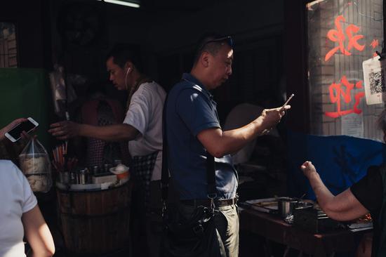 ▲一位顾客在使用微信扫码支付为早餐付款,图自:纽约时报