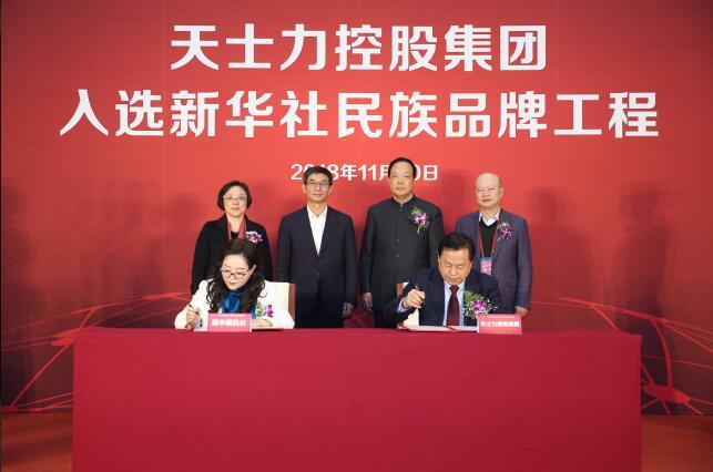 新华社新闻信息中心副主任胡玉霞(左)与天士力控股集团副总裁吴丹勇代表双方签署合作协议