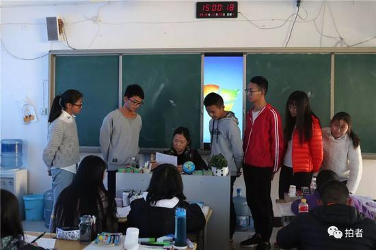 △2018年12月20日,禄劝一中,普通班的英语老师正在挨个问学生考试中遇到的问题。